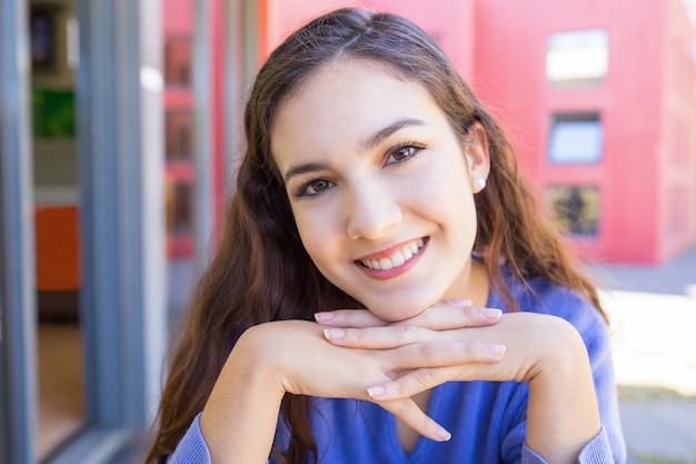 Glückliche junge frau, die draußen an der kamera lächelt