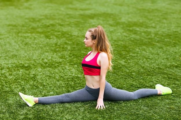 Glückliche junge frau, die draußen in yogaposition sitzt
