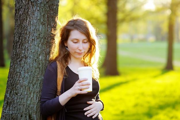 Glückliche junge frau, die draußen kaffee oder tee trinkt
