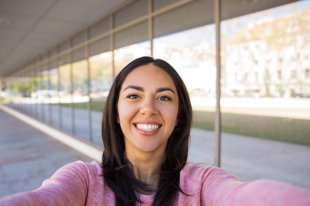 Glückliche junge frau, die draußen selfie foto macht
