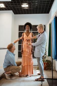 Glückliche junge frau, die ein elegantes kleid trägt, das von zwei beschäftigten modedesignern lächelt