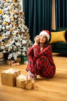 Glückliche junge frau, die ein geschenk nahe weihnachtsbaum wirft. sie sitzt in der nähe von geschenken und geschenken. trendfarben fortuna gold und tidewater green.