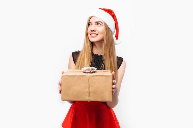 Glückliche junge frau, die ein kleid und eine weihnachtsmütze trägt