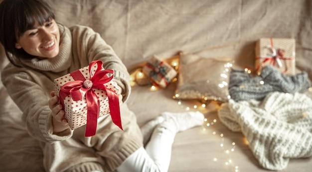 Glückliche junge frau, die ein schön verpacktes weihnachtsgeschenk hält. neujahrs- und weihnachtsfeierkonzept.