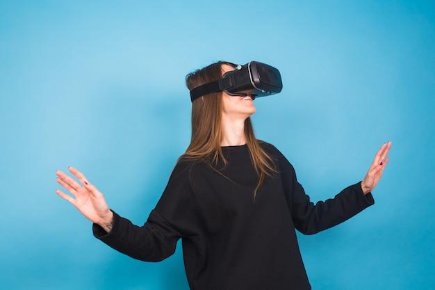 Glückliche junge frau, die ein virtual-reality-headset auf blau verwendet