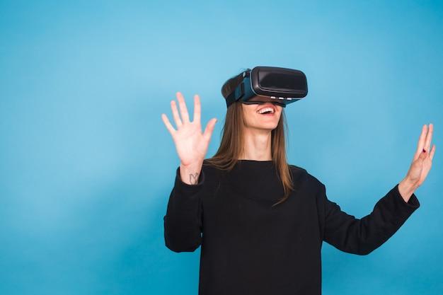 Glückliche junge frau, die ein virtual-reality-headset verwendet.