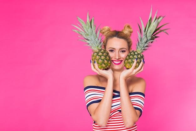 Glückliche junge frau, die eine ananas auf einer rosa wand hält.
