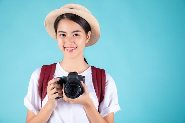 Glückliche junge frau, die eine kamera hält