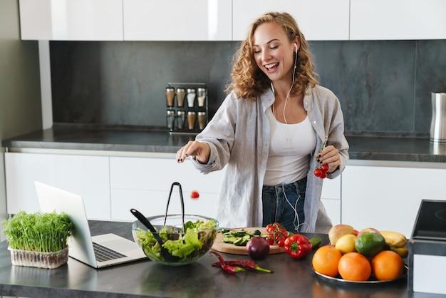 Glückliche junge frau, die einen salat in der küche macht, gemüse hackt, laptop-computer betrachtet, musik mit kopfhörern hört