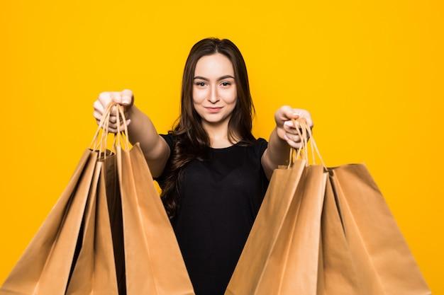 Glückliche junge frau, die einkaufstaschen auf einer gelben wand hält