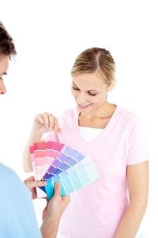 Glückliche junge frau, die farben für das malen eines raumes wählt