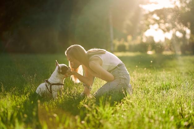 Glückliche junge frau, die französische bulldogge im park küsst