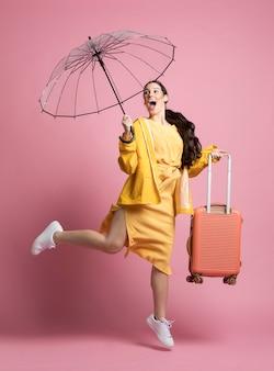 Glückliche junge frau, die geht, während sie einen regenschirm und ihr gepäck hält