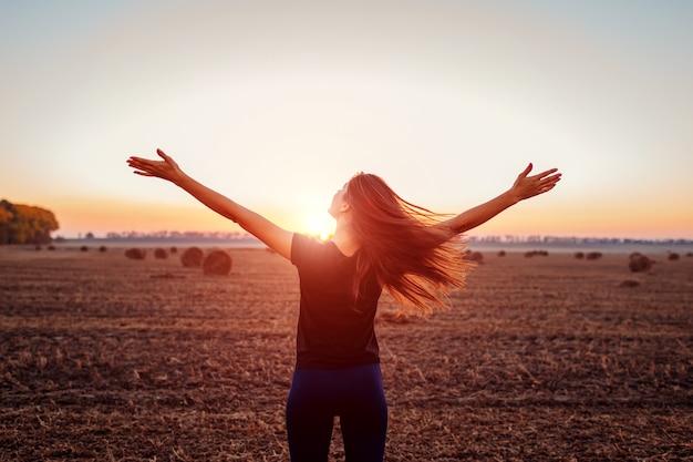 Glückliche junge frau, die geöffnete arme im herbstfeld anhebt und die aussicht bewundert. frau fühlt sich frei. harmonie mit der natur