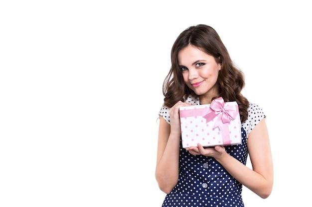 Glückliche junge frau, die geschenk lokalisiert auf weißem hintergrund gibt.