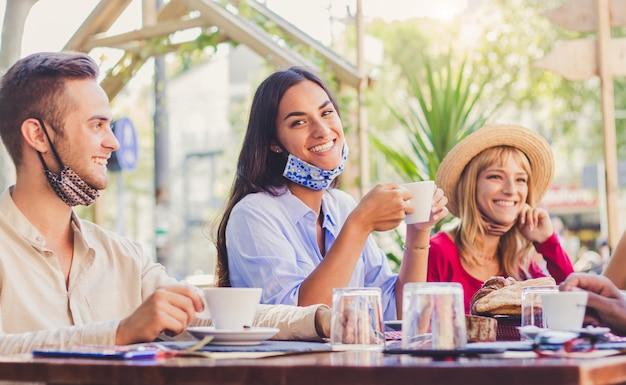 Glückliche junge frau, die gesichtsmaske trägt, die im restaurant lächelt