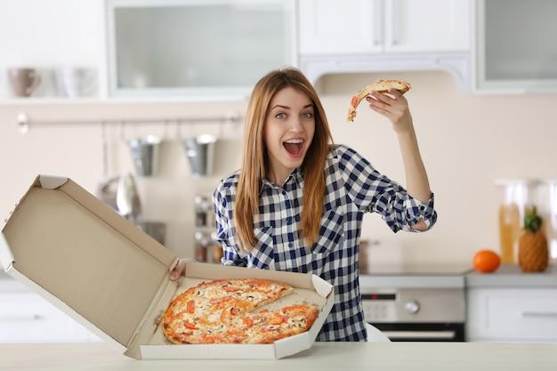 Glückliche junge frau, die heiße pizza im kasten zu hause hält