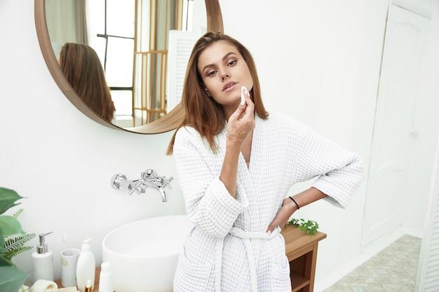 Glückliche junge frau, die ihr gesicht mit wattepads über badezimmer reinigt
