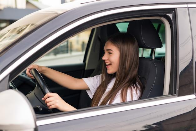 Glückliche junge frau, die ihr neues auto fährt