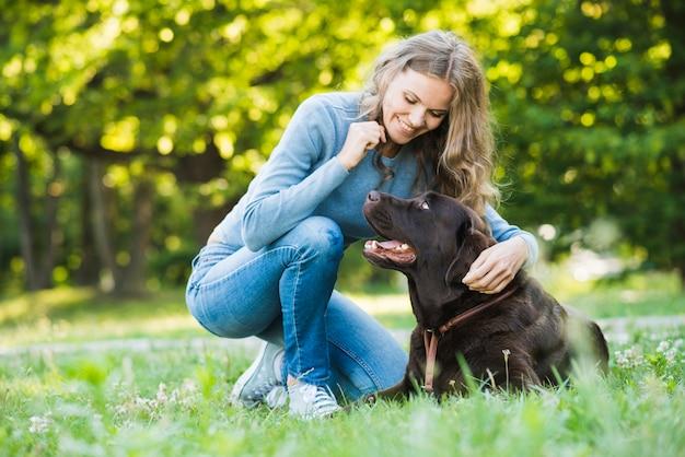 Glückliche junge frau, die ihren hund im park betrachtet