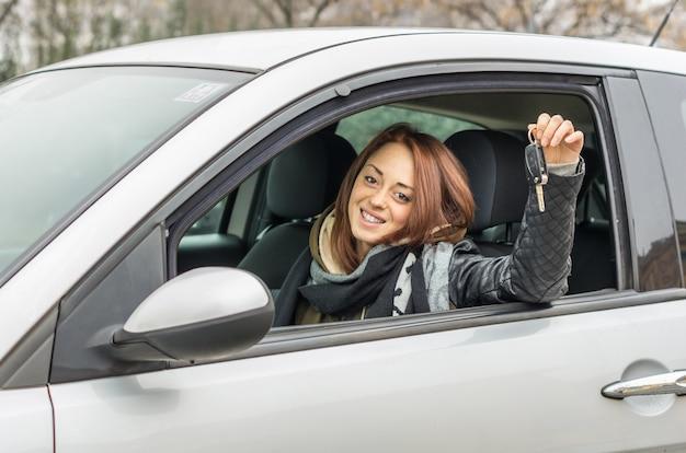 Glückliche junge frau, die im auto lächelnd sitzt