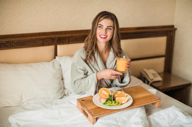 Glückliche junge frau, die im bett frühstückt