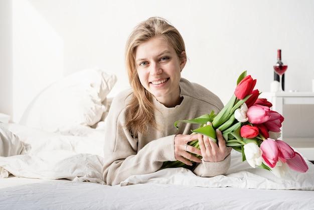 Glückliche junge frau, die im bett liegt und pyjamas hält, die tulpenblumenstrauß halten