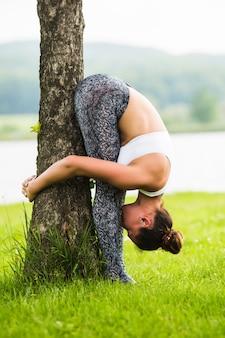 Glückliche junge frau, die in der yoga-haltung auf dem gras im park steht