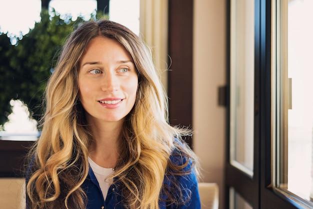 Glückliche junge frau, die in einem restaurant am business-lunch lächelt