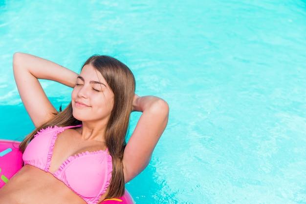 Glückliche junge frau, die in wasser schwimmt