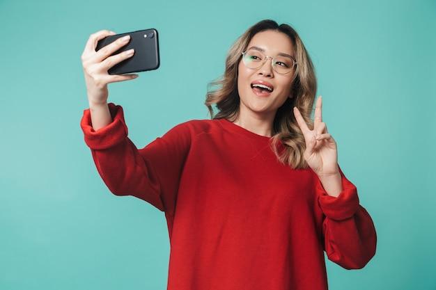 Glückliche junge frau, die isoliert über blauer wand posiert und mit dem handy spricht, macht ein selfie mit friedensgeste