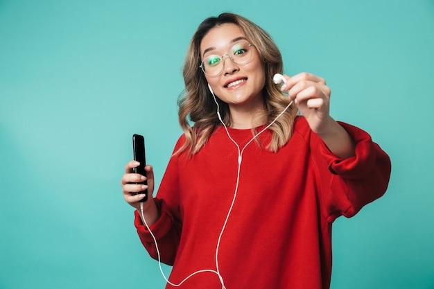 Glückliche junge frau, die isoliert über blauer wand posiert und musik mit kopfhörern über das handy hört