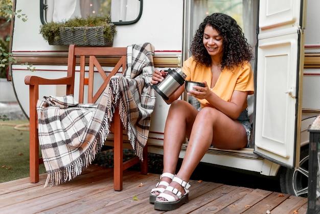 Glückliche junge frau, die kaffee auf einer veranda trinkt