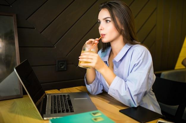Glückliche junge frau, die kaltes getränk im café mit laptop trinkt