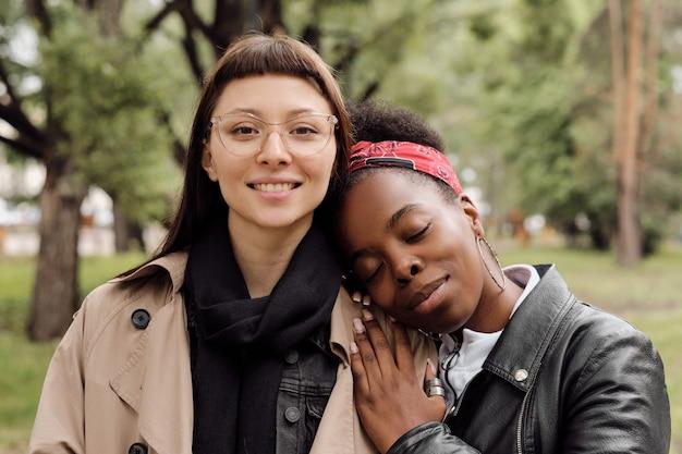 Glückliche junge frau, die kamera anschaut, während ihre freundin den kopf auf ihrer schulter hält