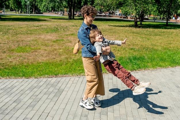 Glückliche junge frau, die lacht, während sie ihren entzückenden kleinen sohn hält und mit ihm auf der straße im park am sonnigen sommertag wirbelt