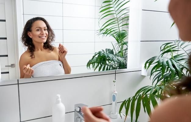 Glückliche junge frau, die lächelt und sich vor dem badezimmerspiegel bewundert