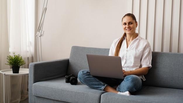 Glückliche junge frau, die laptop zu hause benutzt. auf der couch neben der frau steht eine kamera. der fotograf retuschiert zu hause fotos.
