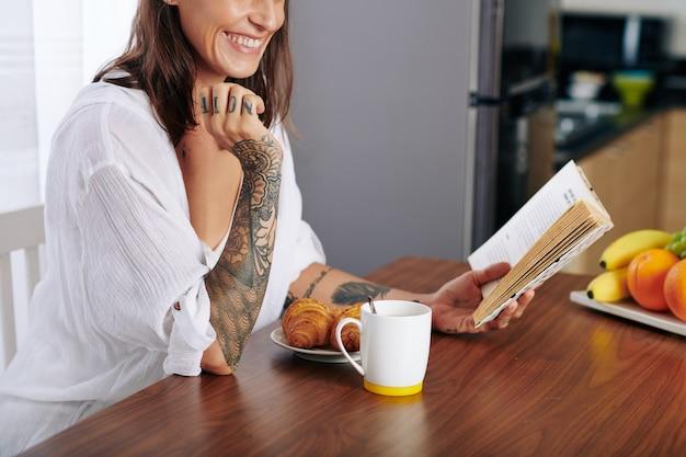 Glückliche junge frau, die lustiges buch liest, wenn sie croissants isst und eine tasse kaffee zum frühstück trinkt