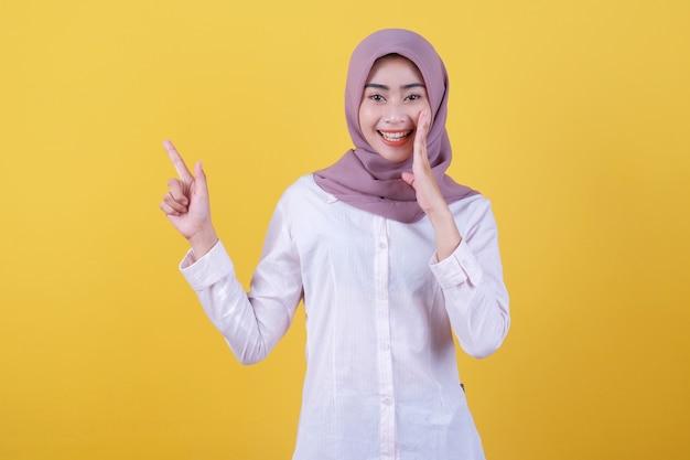 Glückliche junge frau, die mit dem finger auf die linke seite zeigt, hijab trägt und etwas flüstert