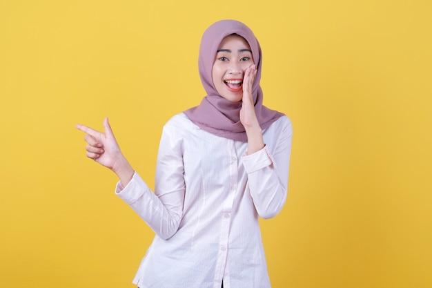 Glückliche junge frau, die mit dem finger auf die linke seite zeigt und mit hijab flüstert