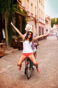 Glückliche junge frau, die mit ihrem freund auf fahrrad reitet