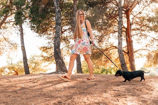 Glückliche junge frau, die mit ihrem haustier im park schlendert