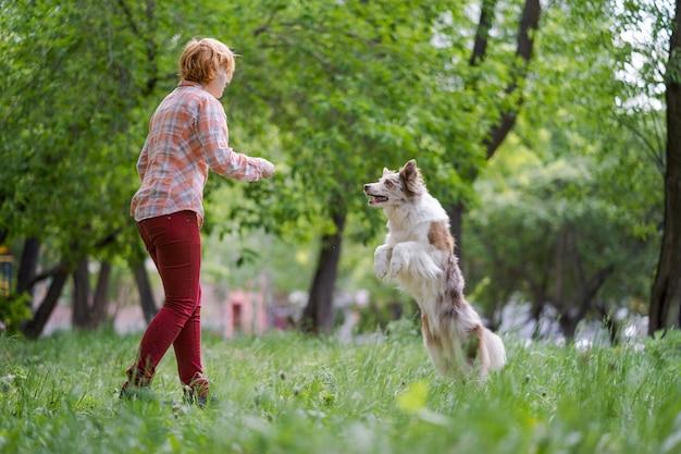 Glückliche junge frau, die mit ihrem hund im park joggt.