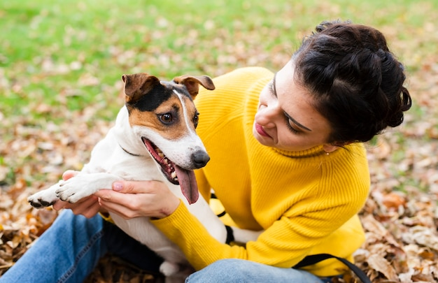 Glückliche junge frau, die mit ihrem hund spielt
