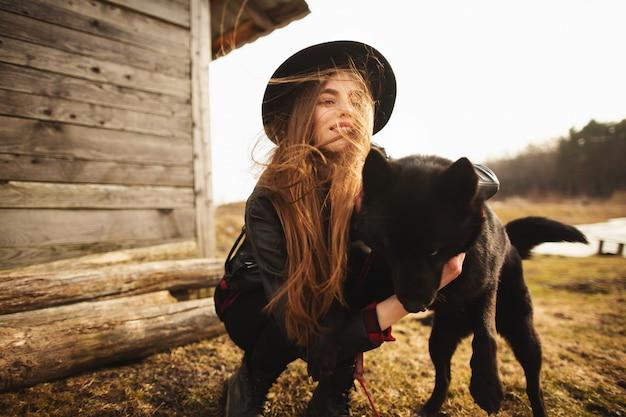Glückliche junge frau, die mit ihrem schwarzen hund plaing ist