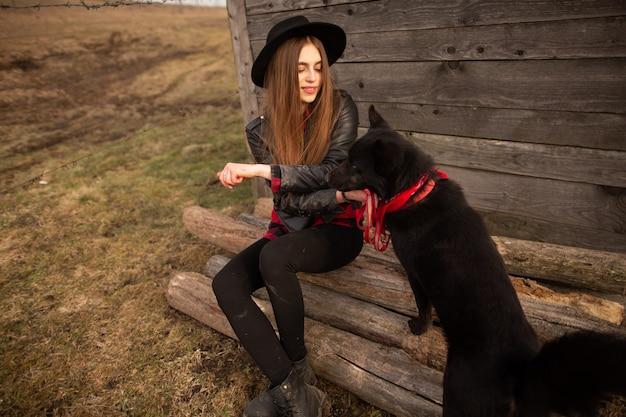 Glückliche junge frau, die mit ihrem schwarzen hund sitzt