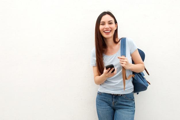 Glückliche junge frau, die mit rucksack und handy steht