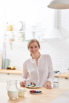 Glückliche junge frau, die morgens geschmackvolle imbisse am licht des küchentischs zubereitet