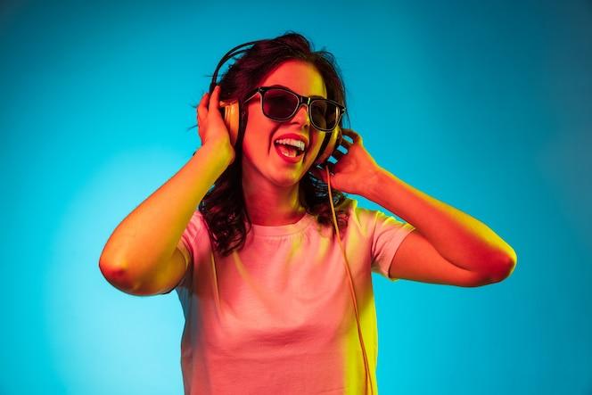 Glückliche junge frau, die musik hört und über trendiges blaues neonstudio lächelt